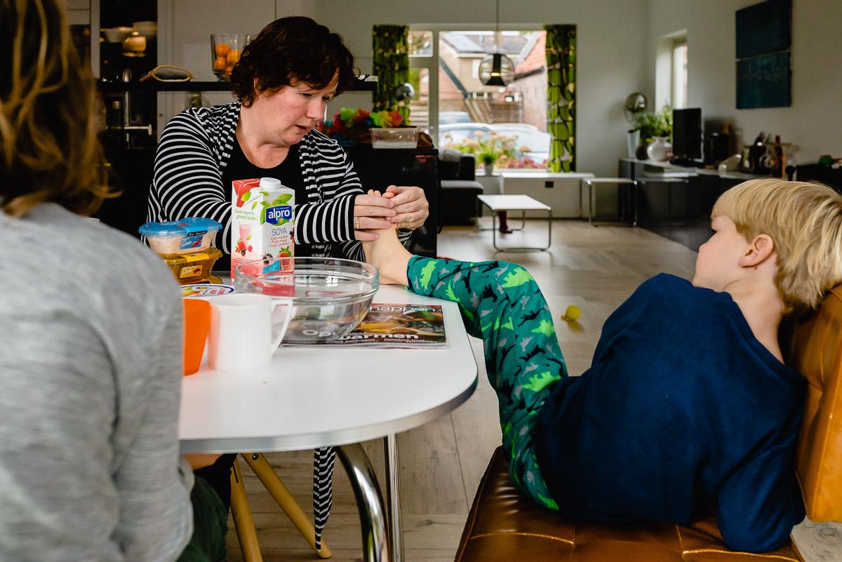 Familie fotografie in Maarssen, documentaire familie fotograaf, voet op tafel, foto door Sandra Stokmans Fotografie
