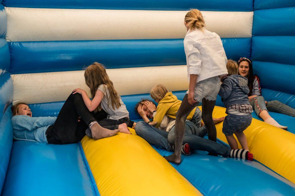 Familiedag fotograferen in Lage Vuursche, documentaire familiefotografie, stoeien in luchtkussen, Sandra Stokmans Fotografie
