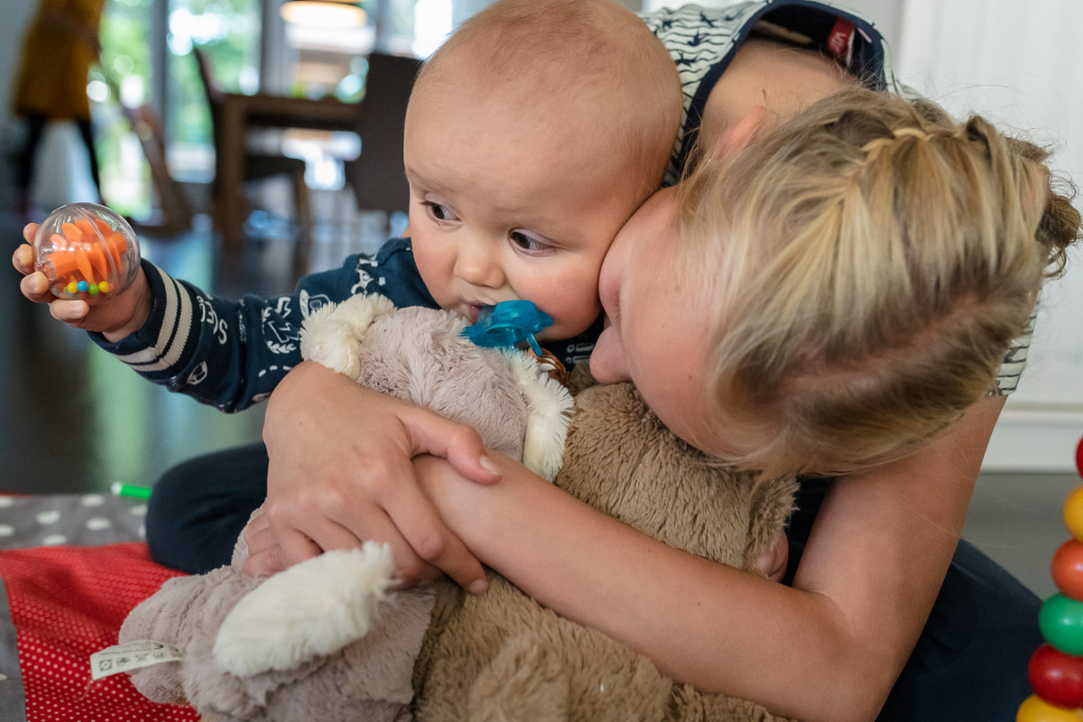Tijdens deze fotosessie van groot gezin, krijgt kleine Jens dikke vette knuffels van zijn grote zus. Familie fotografie, Sandra Stokmans Fotografie