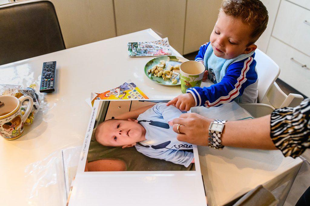 Print your photos, print je foto's, Hartekind Morris kijkt in zijn babyalbum, foto door Sandra Stokmans Fotografie