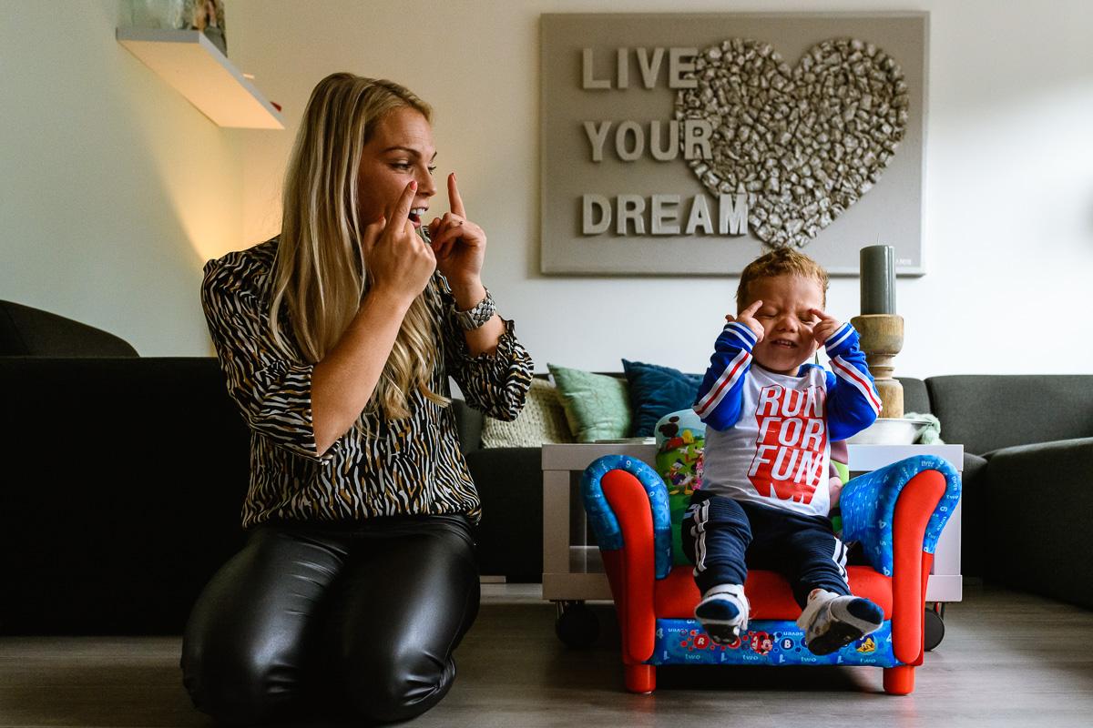 Moeder en zoon bezig met ondersteunende gebaren tijdens documentaire familie reportage chronisch ziek kind. foto foor Sandra Stokmans fotografie