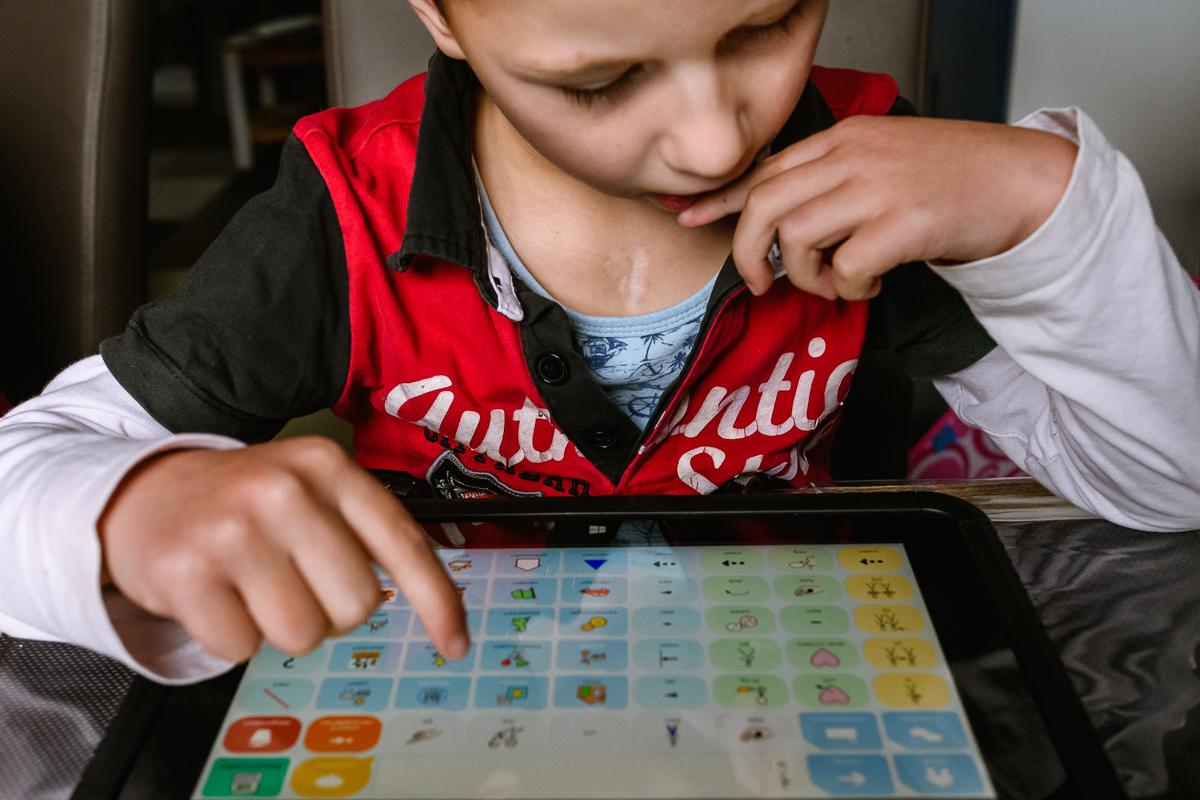 Lucas leert zich beter uit te drukken en de communiceren via het gebruik van een spraakcomputer. Foto door documentaire-familiefotograaf Sandra Stokmans Fotografie